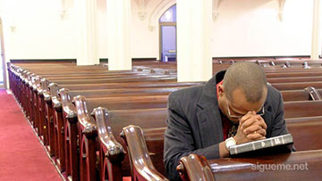 Ministro cristiano orando a Dios en la iglesia