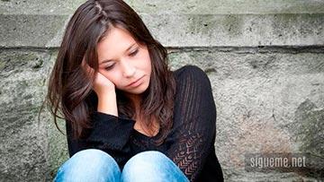 joven adolescente sentada, pensativa, triste