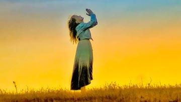 mujer orando a Dios de pie al aire libre