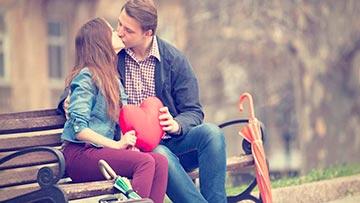 novios cristianos enamorados besandose en un banco de plaza