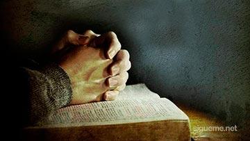 Orando a Dios con las manos sobre la Biblia abierta