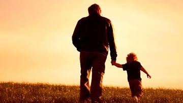 Padre camina junto a su hijo tomados de la mano por el campo