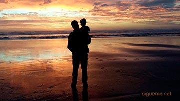 Papa con su hijo en brazos frente al mar al amanecer