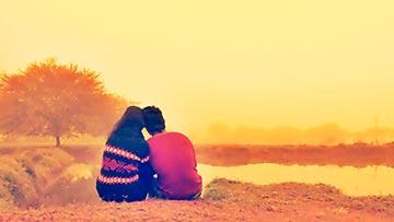 Pareja de Novios cristianos sentados mirando al horizonte