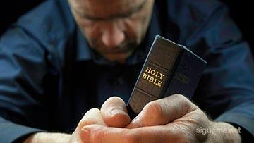 Ministro cristiano orando a Dios y leyendo la Biblia en su devocional