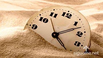 Reloj enterrado en la arena, concepto de postergar, posterga