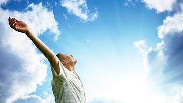 Persona mirando hacia arriba con los brazos en alto